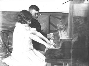 Boy and girl playing piano